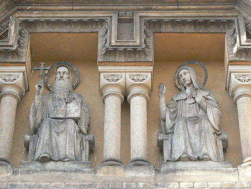 "Statues of St. Benedict and his twin sister, St. Scholastica, above the entrance of the Church of the Annunciation, also called ""St. Gabriel Church"", in Holečkova Street in Prague-Smíchov, Czechia."